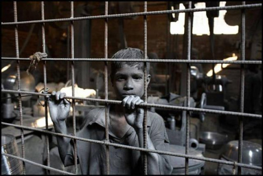 A young boy working in a factory, under deplorable conditions.