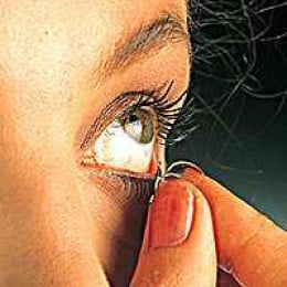 The lens should be held between the thumb and the index finger as it is pulled out from the surface of the eye