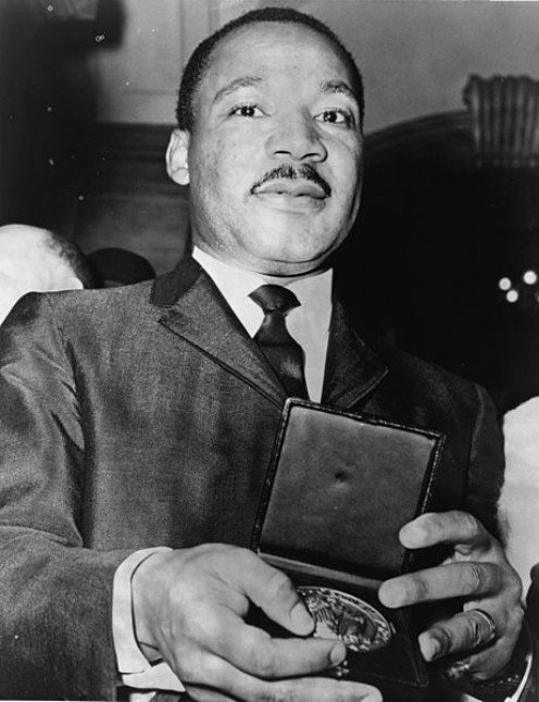 Martin Luther King Jr. is showing a medallion he received from Mayer Wagner in 1964