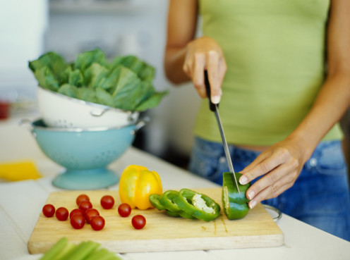 This picture showcases a woman cutting vegetables for a beautiful salad.