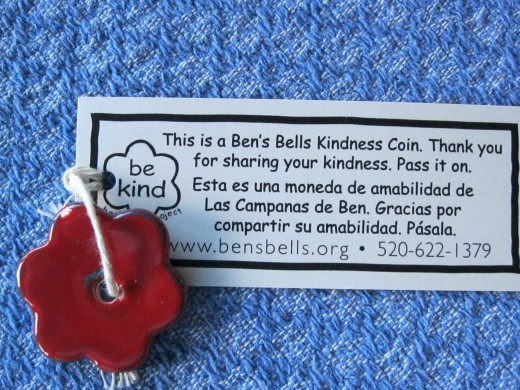 Small Ceramic red flower is a Kindness Coin attached to a card that says Thank you for sharing your kindness.  Pass it on.