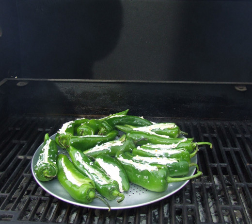 The peppers are placed on the grill. The pan has holes on the bottom to help the peppers cook to perfection.