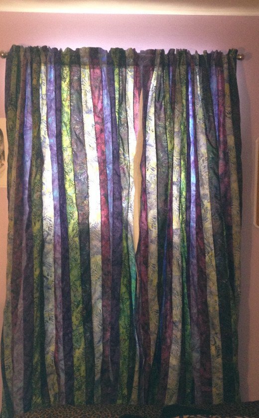 6 Batiks ripped in strips and sewn together with an overlock stitch to prevent fraying and lined with an offwhite thermal but not room darkening lining bring a rainbow in.