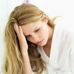 "Picture of depressed woman. This is an article called ""What is Depression."" It lists symptoms of depression. It does not mention the difference between being depressed and clinical depression."