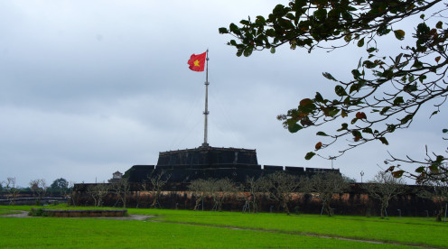 Vietnamese flag flutters over the entrance to Hués vast walled citadel.