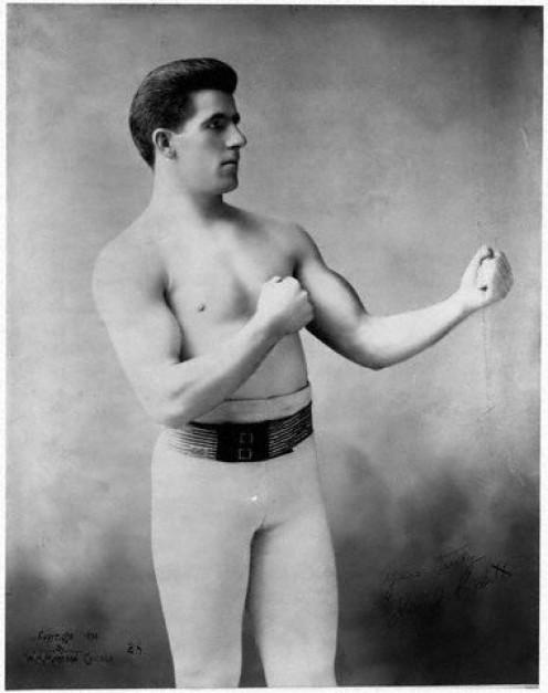 Gentleman Jim Corbett took the heavyweight title from John L. Sullivan in the first gloved boxing heavyweight title tilt.
