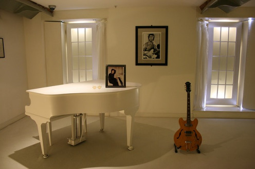 Display of John Lennon portraits and guitar.