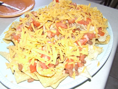 Image  Loaded Nachos. All of the Ingredients layred on Top the Way You Desire. Add Cheese on Top.