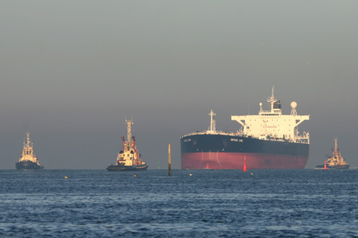 Incoming tanker for Teesport's oil terminal with pilot tugs passes the South Gare beacon
