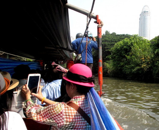 These Chinese visitors to Bangkok are enjoying their boat trip down Bangkok's less well known waterways...