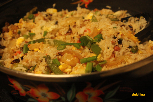 Add cooked rice in the wok and top it with fried veggies, scrambled eggs and some required seasonings.
