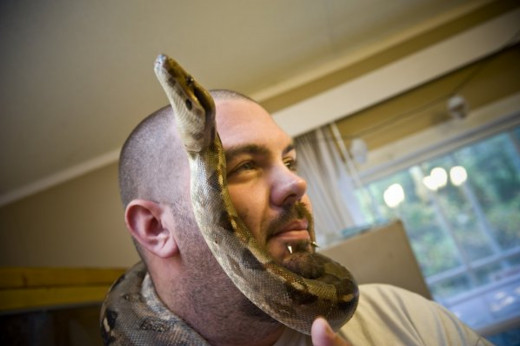 Chris & Jellybean– Chris with one of the family pets, Jelly Bean, an albino boa.