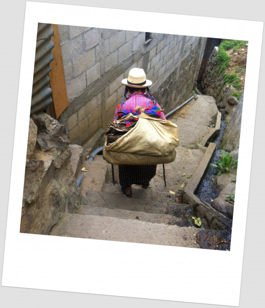 An old woman carrying a sack of wood strapped to her head for her stove (San Antonio, Lago de Atitlan)