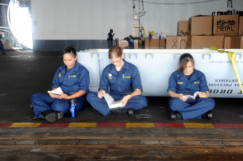 """US Navy...Midshipman take a few minutes during their lunch break to read in the hangar bay of the aircraft carrier USS Dwight D. E."""
