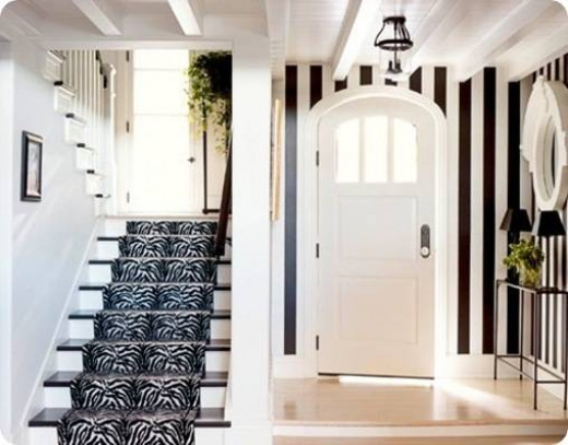 bold striped walls in black and white with a stairway runner in disctincitve black and white