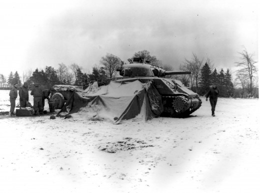 Tankmen of the U.S. First Army gather around a fire on the snow-covered ground near Eupen, Belgium, opening their Christmas packages (12/30/44) -5th Armd. Regt.""