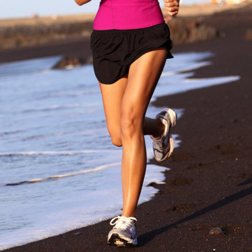 toned legs on a female running in black shorts and sneakers on a beach