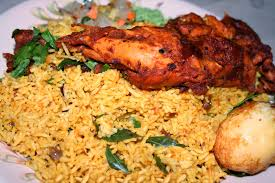 A Biryani served with Tandoori Chicken and a hard boiled egg.