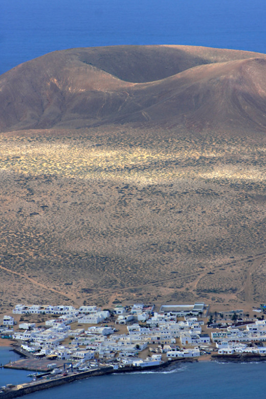 Volcanic crater and the town of Caleta de Sebo - principal settlement on La Graciosa