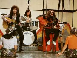 Jeff Lynne, Bev Bevan and Roy Wood of the Move weirdly play in front of some girls who are near waist deep in water.