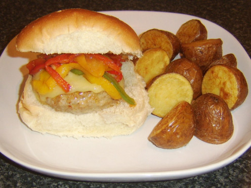 Fried bell peppers top a spicy pork cheeseburger which is served with deep fried red potato halves