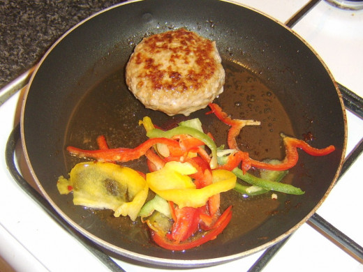 Bell peppers are added to pan with partly fried pork burger