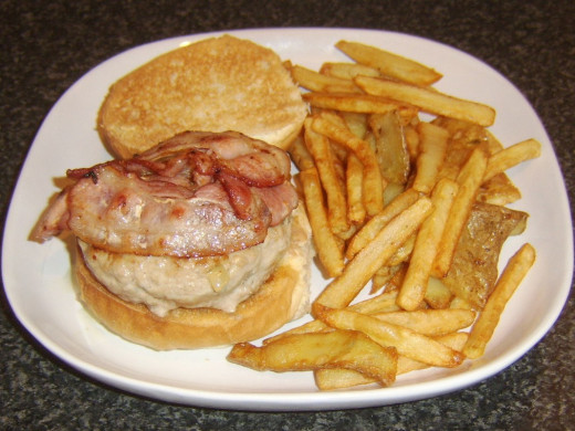 Bacon slices are laid on pork, sage and onion burger