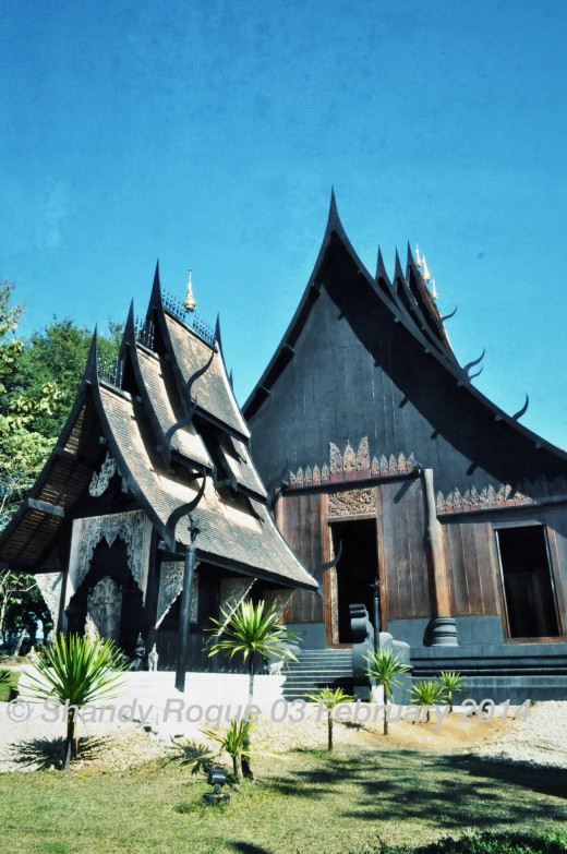 The main house of the dark Baan Dam is a large wooden structure with a multi-tiered roof that has protruding spikes that look like devil's horns.