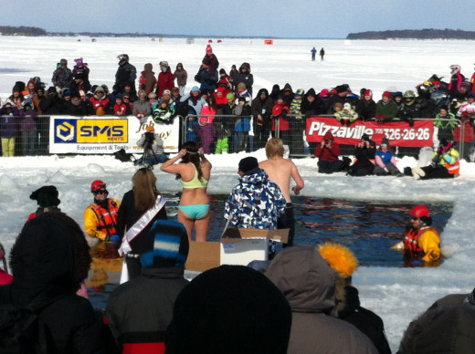 In this picture you can see two people in swim suits getting ready to jump into the frigid water of Lake Couchiching at Orillia's 2014 Polar Bear Dip.