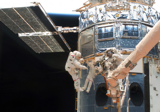 Astronauts John Grunsfeld, left, and Andew Feustel working on the Hubble Space Telescope