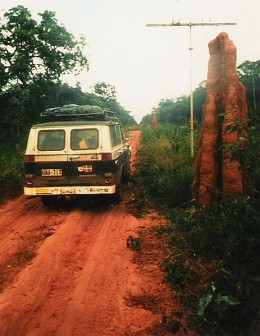 Van driving by a large termite mound.