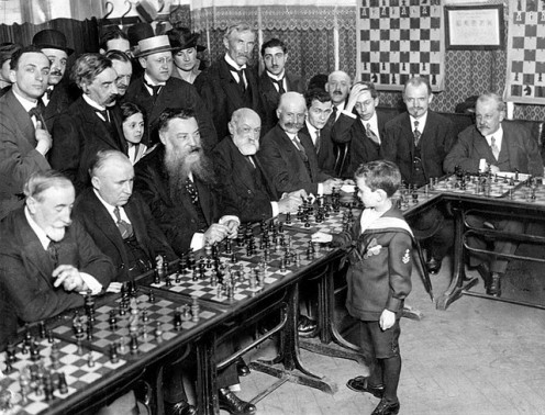 A chess prodigy plays with experienced playersin a tournament.