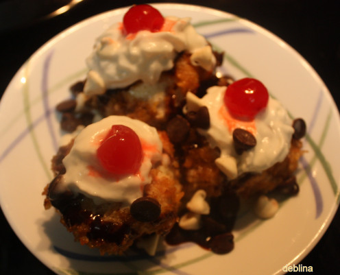 Place them in a plate. Sprinkle chocolate sauce, whipped cream, cherries and chocolate chips and serve immediately.