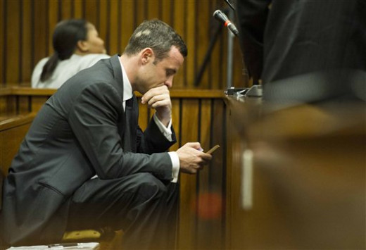 Oscar Pistorius on his cellphone during the trial and questioning of witnesses.