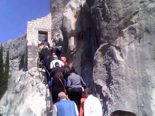 The entrance of the castle with many people climbing up to see the interesting treasures and to know more about the  intriguing history