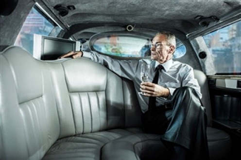 An old rich man in his limo loves him an expensive tuxedo.