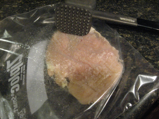 Place chicken between sheets of waxed paper or in a plastic bag. Pound to even thickness.