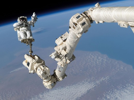 An astronaut working on his equipment in the outer space