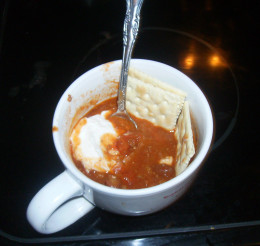 Cup of homemade chili with crackers and sour cream