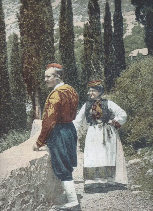 A traditionally dressed couple   standing  at the old castle