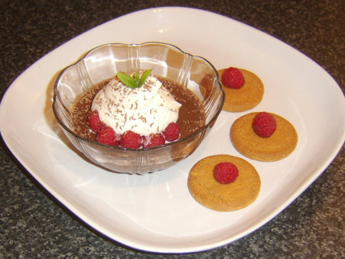 Fresh raspberries and cream on a coffee, chocolate and ginger jelly served with ginger biscuits