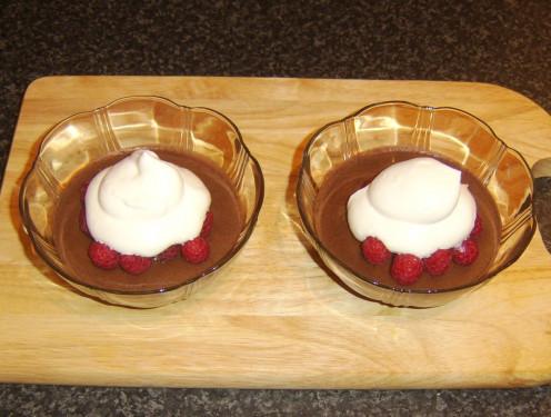 Whipped cream spooned on to fresh raspberries