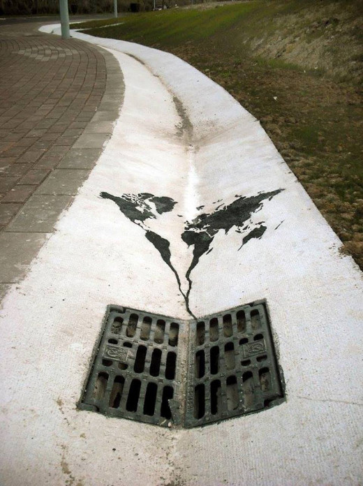 This artists work are scattered around Spain and Russia. This one shows the world literally going down the drain. What's note-worthy is the positioning of the world, with the lower hemisphere filtering directly down the sewer.