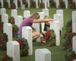 Mother and son visit the grave of their husband and father, a KIA soldier, at South Florida National Cemetery.