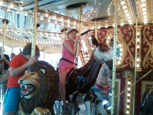 Olivia seated on a mock Okapi, one of the zoo's represented animals on the carousel.