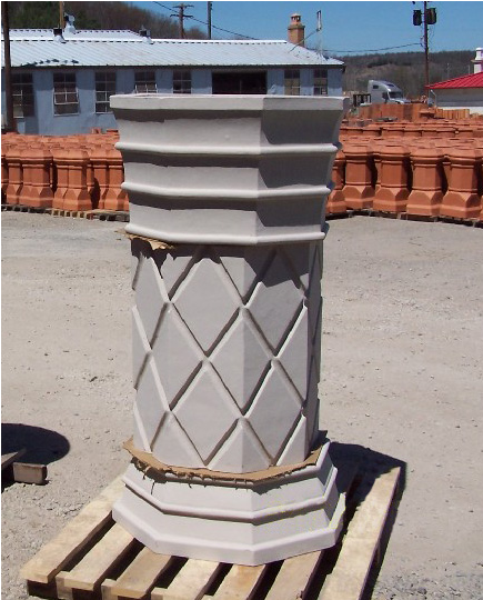 A finished clay chimney pot on a pallet.