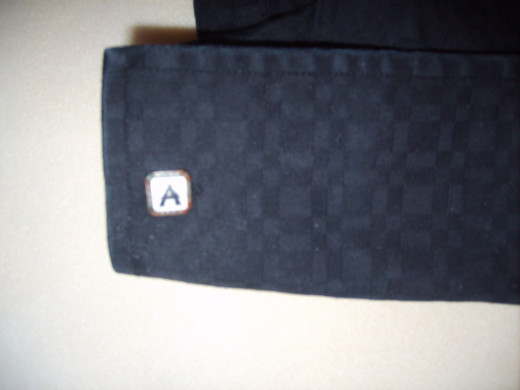 A monogrammed cufflink stands out on this black shirt