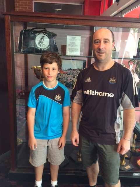 The author, Michael, with son Sam at the Port Adelaide Football Club, in front of the Trophy stand. Magpie supporters are the same the world over!