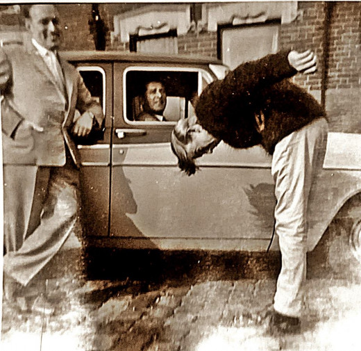 My brother in his youth, fooling around outside our house, with our dad on the left and grandad in his car.