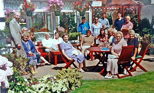 The gathering at the Coach House for dad's surprise 70th birthday party. Dad is standing on the right, in a pink shirt. Mum is seated on the left in a blue suit.
